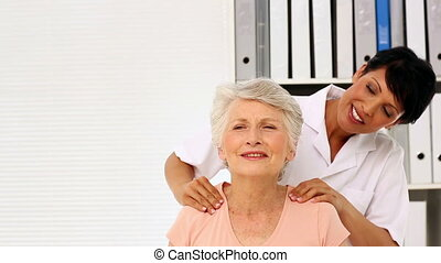 Nurse rubbing elderly patients shoulders in office at the...