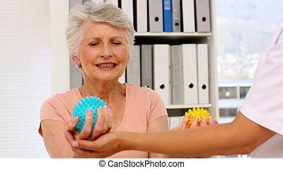 Nurse showing elderly patient how to use massage balls in...