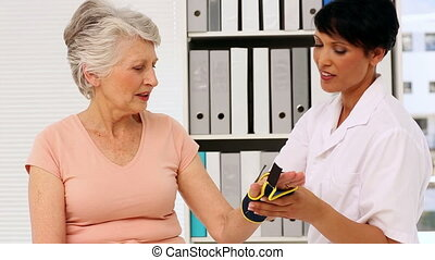 Nurse showing elderly patient how to put on wrist brace in...