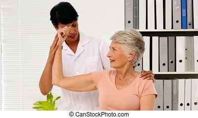 Nurse showing elderly patient how to exercise her injured...