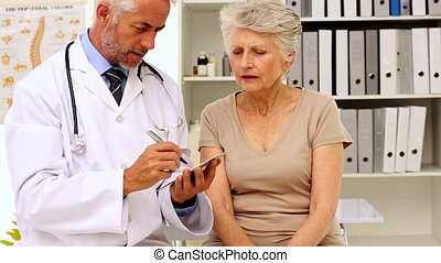 Doctor explaining a prescription to his patient in his...