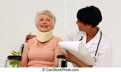 Nurse talking with elderly patient in a wheelchair in office...