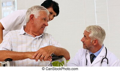 Doctor talking with elderly patient in a wheelchair being...