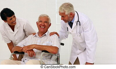 Doctor and nurse talking with elderly patient in a...