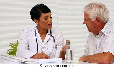 Doctor explaining medicine to patient in office at the...