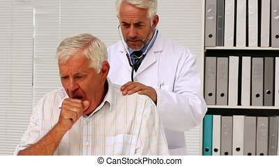 Doctor examining his senior patient who has a cough in...