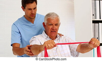 Male nurse showing elderly patient how to use resistance...