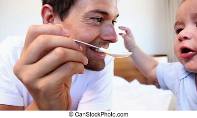 Happy father feeding his baby son at home in bedroom