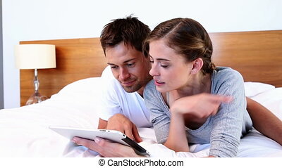Happy couple lying on bed using tablet together at home in...
