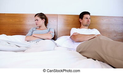 Unhappy couple not talking after argument at home in bedroom