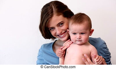 Pretty mother holding baby boy on white background