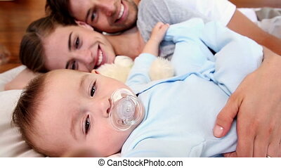 Happy parents lying on bed with baby son at home in bedroom