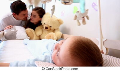 Happy parents watching over baby in crib - Happy parents...