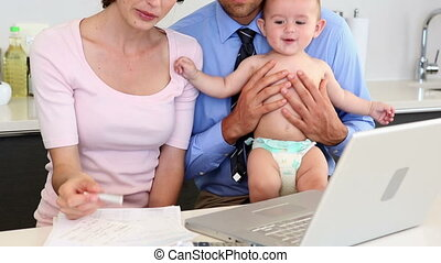 Parents using laptop with their baby son and calculating...