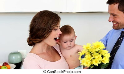 Father surprising mother holding baby with flowers - Father...