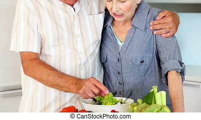 Senior couple preparing a healthy salad at home in the...