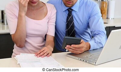 Stressed couple calculating bills at home in the kitchen