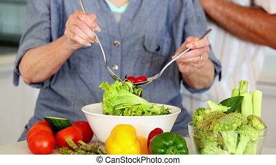 Senior couple preparing a healthy salad together at home in...