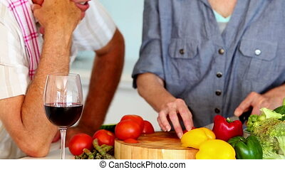 Senior couple preparing a healthy meal while drinking red...