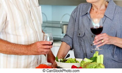 Senior couple preparing a healthy salad while drinking red...