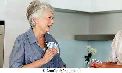 Senior couple playing cards at the counter at home in the...