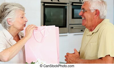 Senior man giving his partner a present in a pink bag at...