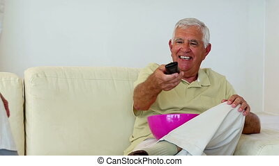 Senior couple sitting on sofa watching tv at home in the...