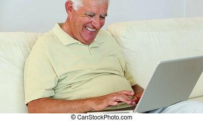 Senior man sitting on sofa using l - Senior man sitting on...