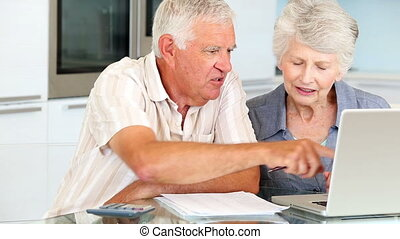 Senior couple using laptop to pay their bills at home in the...