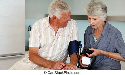 Senior woman taking her husbands blood pressure at home in...
