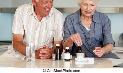Senior couple organizing their medicine for the week at home...