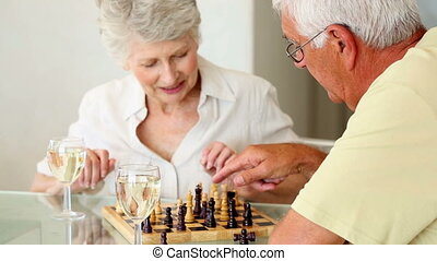 Senior couple sitting at table playing chess at home in the...