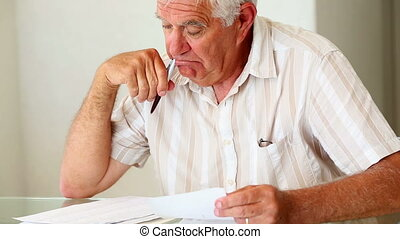 Senior man sitting at table working out bills at home in the...