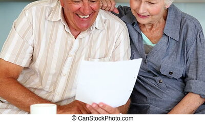 Senior couple organizing their bills at home in the kitchen...