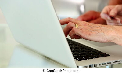 Senior couple using laptop to shop online at home in the...