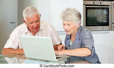 Senior couple using laptop together at home in the kitchen