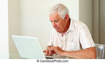 Senior man using laptop at the tabl