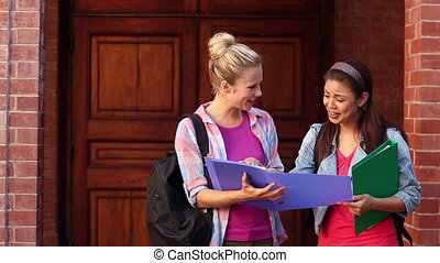 Happy students looking at folder together on college campus