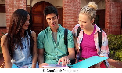 Happy students chatting together ou