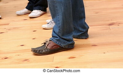 Feet standing in a circle on wooden floor