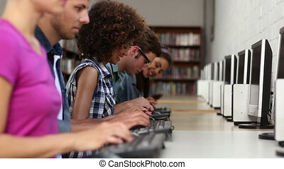 Students sitting in a row working on computers in college