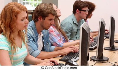 Students working in computer room with lecturer at the...
