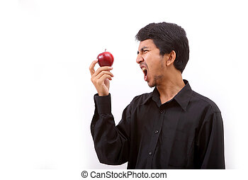 Young healthy man eating a red apple