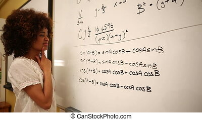 Confused student looking at maths on whiteboard at the...