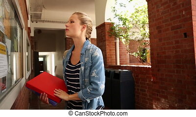 Blonde student checking the noticeboard at the university