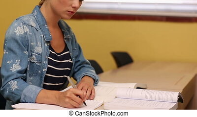 Blonde student taking notes in classroom