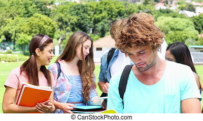 Handsome student smiling at camera with classmates behind on...