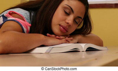Pretty student sleeping at desk in classroom at the...