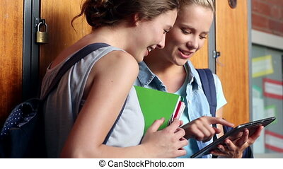 Classmates standing in hallway using tablet pc at the...