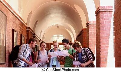 Classmates standing in hallway celebrating - Classmates...